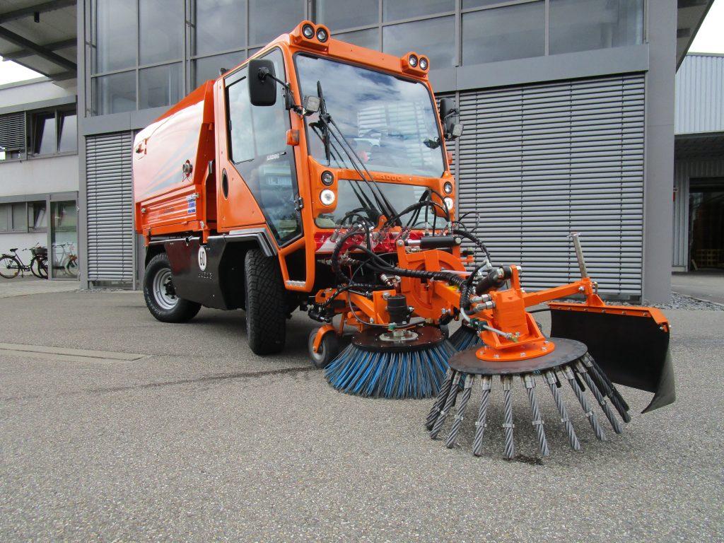 T1250 mit Frontkehraggregat, Wildkrautbürste und Kehrmaschinenaufbau K2